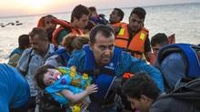 In this Aug. 13, 2015 file photo, a man carries a girl in his arm as they arrive with other migrants just after dawn on a dinghy after crossing from Turkey to the island of Kos in southeastern Greece. The question of what to do about the world's 65 million displaced people takes centre stage at the United Nations General Assembly Monday, Sept. 19, 2016. (Alexander Zemlianichenko/AP)