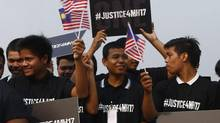 Youths hold placards and Malaysian flags during a Malaysia Airlines flight MH17 solidarity gathering outside the Parliament house in Kuala Lumpur on July 23, 2014. (SAMSUL SAID/REUTERS)