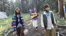 Collin, from left, Noah, and Dave enjoy some music during their morning stroll back to the Instant Soup Kitchen at the Rainbow Gathering, July 2, 2008. The Rainbow Family is a loosely knit counterculture group that gathers on federal lands around the U.S. each year, usually in early July. (Tim Kupsick/AP)
