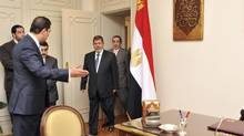 President-elect Mohamed Morsi, middle, arrives to his office at the Presidency in Cairo on Monday. (HANDOUT/REUTERS)