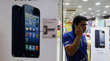 A man speaks on his mobile phone while standing next to posters advertising an Apple iPhone 5 and Blackberry Z10 in Ahmedabad Feb. 22, 2013. More than four years after it started selling iPhones in India, Apple Inc. is now aggressively pushing the device through instalment payment plans that make it more affordable, a new distribution model and heavy marketing blitz. (AMIT DAVE/REUTERS)