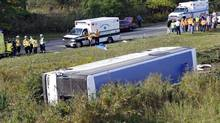 Rescue workers stand by after a bus overturned in a ditch at an exit ramp off Route 80 in Wayne, N.J. Saturday, Oct. 6, 2012. The chartered tour bus from Toronto carrying about 60 people overturned on an interstate exit ramp. (Bill Kostroun/AP)