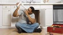 Man sitting on floor with pipe (JupiterImages/(C) 2007 Thinkstock Images)