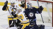 Pittsburgh Penguins' Jake Guentzel (59) and Sidney Crosby (87) celebrate Guentzel's goal on Winnipeg Jets goalie Michael Hutchinson (34) during third period NHL action, in Winnipeg on Wednesday, March 8, 2017. (JOHN WOODS/THE CANADIAN PRESS)