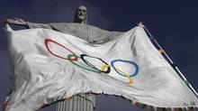 "The Olympic Flag flies in front of ""Christ the Redeemer"" statue during a blessing ceremony in Rio de Janeiro August 19, 2012. (RICARDO MORAES/REUTERS)"
