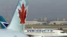 An Air Canada jet sits at a gate as a Westjet heads for it's gate in this file photo. (Fred Lum/The Globe and Mail)