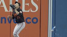 A beer can lands near Baltimore Orioles leftfielder Hyun Soo Kim as he gets set to catch a fly ball during the seventh inning of the wild-card game against the Toronto Blue Jays in Toronto, Tuesday, Oct.4, 2016. (Frank Gunn/The Canadian Press)
