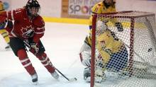 Canada's Haley Irwin (21) scores on Sweden's Valentina Lizzna (35) during first period of IIHF Women's World Hockey Championship exhibition game in Pembroke, Ontario Saturday March 30, 2013. IIHF Women's World Hockey Championship starts in Ottawa on Tuesday. (FRED CHARTRAND/THE CANADIAN PRESS)