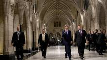 U.S. Secretary of State John Kerry (C) and his Canadian counterpart John Baird (R) walk through the Hall of Honor on Parliament Hill in Ottawa, Canada, October 28, 2014. Kerry said on Tuesday that the attack on the Canadian parliament and the country's National War Memorial last week in which a soldier was killed was clearly a terrorist act. (POOL/REUTERS)