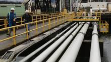 Workers walk to a jet fuel barge at Kinder Morgan's Westridge Terminal on Burrard Inlet in Burnaby, British Columbia, Canada November 18, 2016. (CHRIS HELGREN/REUTERS)