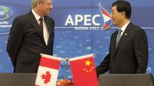Canadian Prime Minister Stephen Harper speaks with Chinese President Hu Jintao following a signing ceremony at the APEC Summit in Vladivostok, Sunday September 9, 2012. (Adrian Wyld/THE CANADIAN PRESS)