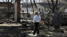 A woman walks through an area impacted by Superstorm Sandy in Breezy Point, Sunday, Nov. 4, 2012, in New York. (Kathy Willens/AP)