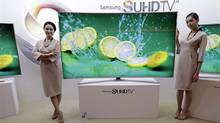 In this Jan. 5, 2015 photo, models pose with a Samsung Electronics Co.' SUHD 4K smart TV during a press conference in Seoul, South Korea. Samsung Electronics Co. on Tuesday, Feb, 10, 2015, said voice recognition technology in its Internet connected TVs can capture and transmit nearby conversations.(AP Photo/Ahn Young-joon)