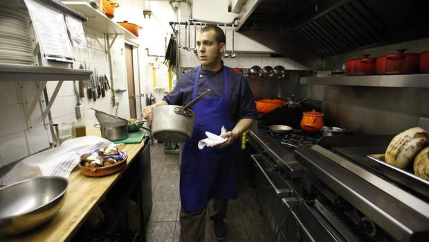 Chef Michael Caballo prepares food including the Chantecler Chicken Baked In Hay at Edulis restaurant at 169 Niagara Street in Toronto on June 1, 2012.