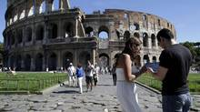 Tourists use an iPad in front of Rome's Colosseum. Global tourism has largely rebounded from the 2008 recession, according to the United Nations World Tourism Organization. (TONY GENTILE/REUTERS)