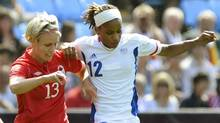 France's Elodie Thomis (12) tries to get around Canada's Sophie Schmidt in the women's bronze medal soccer match in Coventry at City of Coventry Stadium at the London 2012 Olympic Games August 9, 2012. (Reuters)