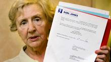 Margaret Davis holds up an agreement between her and Earl Jones at an information meeting along with other investors in Montreal, Sunday, July 12, 2009. Quebec's financial market authority has frozen the assets of the financial advisor. (Graham Hughes)