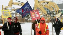 In this January 26, 2012 photo, Caterpillar-owned Electro-Motive workers picket a Caterpillar equipment dealership in London, Ont. (DAVE CHIDLEY/DAVE CHIDLEY/THE CANADIAN PRESS)