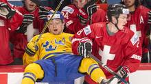 Sweden's Rasmus Dahlin, left, is checked into the bench by Switzerland's Jerome Portmann (8) during first period IIHF World Junior Championship hockey action, in Montreal on Wednesday, December 28, 2016. (Ryan Remiorz/THE CANADIAN PRESS)