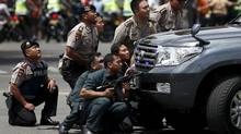 Police officers react near the site of a blast in Jakarta, Indonesia, on Thursday. Amid several explosions and gunfire in the capital city, the city's highest-profile attack in six years, two civilians were killed: a Canadian and an Indonesian. (DARREN WHITESIDE/REUTERS)