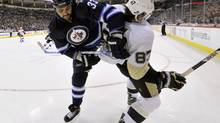 Winnipeg Jets' Dustin Byfuglien, left, checks the Pittsburgh Penguins' Sidney Crosby during the second period of their NHL hockey game in Winnipeg January 25, 2013. (FRED GREENSLADE/REUTERS)