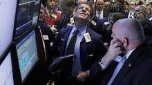 Trader Sean Spain, center, checks the prices as he waits for the IPO of National Bank Holdings Corp., of Greenwood Village, Colo., to begin trading on the floor of the New York Stock Exchange Thursday, Sept. 20, 2012. (Richard Drew/AP)