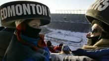 Hockey fans sit in the stands wearing puck hats during the NHL Oldtimers game outdoors at Commonwealth Stadium in Edmonton, November 22, 2003. The Edmonton Oilers and the Montreal Canadiens met in the first ever National Hockey League game played outdoors. (Reuters)