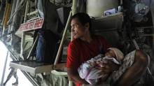 Manuel Aballe, left, holds his two-month-old daughter, Richelyn, aboard a government plane waiting to leave Tacloban. Debris-clogged roads have challenged aid efforts, and officials found themselves on the defensive Tuesday over the pace of relief work as Manila struggled to get supplies to the airport in Tacloban. (jES AZNAR/NYT)