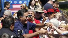 U.S. Republican presidential candidate Mitt Romney shakes hands with people along the parade route as he takes part in the Wolfeboro Fourth of July Parade in Wolfeboro, N.H. (Jessica Rinaldi/Reuters)
