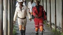 Miners walk at the end of their shift at Anglo Platinum's Khuseleka mine in Rustenburg, northwest of Johannesburg, Jan. 15, 2013. (SIPHIWE SIBEKO/REUTERS)