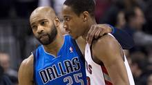 Toronto Raptors forward DeMar DeRozan, right, is hugged by Dallas Mavericks forward Vince Carter, left, after the Raptors defeated the Mavericks during second half NBA action in Toronto on Wednesday, January 22, 2014. (Nathan Denette/THE CANADIAN PRESS)