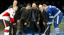 Hockey Hall of Fame inductees Joe Nieuwendyk, back left, Doug Gilmour, back second left, Ed Belfour, centre back, Mark Howe, back left, take part in a puck drop ceremony with Toronto Maple Leafs defenceman Dion Phaneuf, front right, and Ottawa Senators Daniel Alfredsson, front left, before the start of NHL hockey action in Toronto on Saturday, Nov. 12, 2011. THE CANADIAN PRESS/Nathan Denette (Nathan Denette/CP)