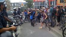 Photo of protesters aboard bikes chanting 'let us ride!' as they try to break through police barricade at Bloor and Spadina in Toronto, Sunday June 27. (Laura Blenkinsop For The Globe and Mail)