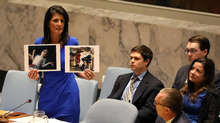 U.S. Ambassador to the United Nations Nikki Haley holds photographs of victims during a meeting at the United Nations Security Council on Syria at the United Nations Headquarters in New York on Wednesday. (SHANNON STAPLETON/REUTERS)