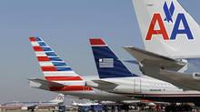 U.S. Airways and American Airlines planes are shown at Dallas/Fort Worth International Airport Thursday, Feb. 14, 2013, in Grapevine, Tex. The two airlines will merge forming the world's largest airlines. (LM Otero/AP)