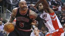 Chicago Bulls power forward Carlos Boozer goes to the net against Toronto Raptors power forward Amir Johnson (R) during the second half of their NBA game in Toronto, January 16, 2013. (MARK BLINCH/REUTERS)