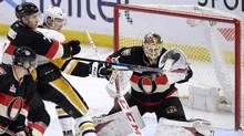 Ottawa Senators goalie Mike Condon reaches for the puck as Kyle Turris wraps up Pittsburgh Penguins' Oskar Sundqvist during third period NHL hockey action in Ottawa, on March 23, 2017. (Justin Tang/THE CANADIAN PRESS)