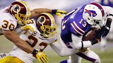 Buffalo Bills' Stevie Johnson (13) tries to get past Washington Redskins' LaRon Landry (30) and DeAngelo Hall (23) during the first half of an NFL football game in Toronto on Sunday, Oct. 30, 2011. (AP Photo/Derek Gee) (Derek Gee)