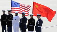 A colour guard of U.S. and Chinese flags awaits the plane of China's President Hu Jintao at Andrews Air Force Base, Maryland in this April 12, 2010 file photo. U.S. President Barack Obama unveiled a defense strategy on Jan. 5, 2012 that would expand the U.S. military presence in Asia but shrink the overall size of the force. (Jonathan Ernst/Reuters/Jonathan Ernst/Reuters)