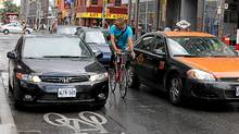 In this file phioto, a cyclist yells at the driver of an illegally parked car during rush hour on Wellesley Avenue near Yonge street in Toronto. (Deborah Baic/Deborah Baic/The Globe and Mail)