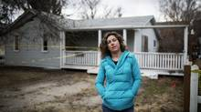 Darcie Lloyd in front of the house she lost to the flood last year in the Bowness community of Calgary, Alberta, April 25, 2014. (Todd Korol for The Globe and Mail)