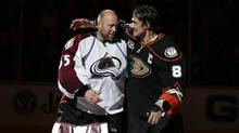 Anaheim Ducks' Teemu Selanne, right, of Finland, and Colorado Avalanche goalie Jean-Sebastien Giguere, who plan to retire after the season, hug as they are honored after an NHL hockey game on Sunday, April 13, 2014, in Anaheim, Calif. (Jae C. Hong/AP)