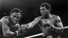 In this Oct. 1, 1975, file photo, spray flies from the head of Joe Frazier as Muhammad Ali connects with a right in the ninth round of their title fight in Manila, Philippines. Ali won the fight on a decision to retain the title. The two fought three times, including two of the most famous matches ever. (MITSUNORI CHIGITA/AP)