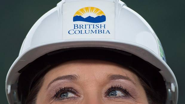 Wearing a hard hat, B.C. Premier Christy Clark listens to a question at the Woodfibre LNG project site near Squamish, B.C., on Friday November 4, 2016. Clark never seems to miss the chance to put on a hard hat and pose with workers for what has become the trademark photo opportunity of her government. (DARRYL DYCK/THE CANADIAN PRESS)