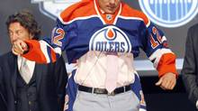 Nail Yakupov, a winger from Russia who was chosen first overall by the Edmonton Oilers in the first round of the NHL hockey draft, pulls on an Oilers jersey on Friday, June 22, 2012, in Pittsburgh. (Keith Srakocic/AP)