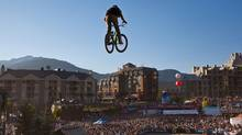 Spectators in Whistler Village watch as a rider flies off of the final jump during the finals of the Monster Energy Slopestyle Finals at the Crankworx Freestyle Mountain Bike Series in Whistler Saturday, August 14, 2010. (Brett Beadle For The Globe and Mail)