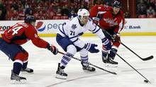 Toronto Maple Leafs right wing David Clarkson skates with the puck between Washington Capitals centre Mikhail Grabovski and defenceman John Erskine during the second period of an NHL hockey game, Friday, Jan. 10, 2014, in Washington. (Associated Press)