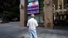 File photo of a man watching the Toronto stock market activity on a screen posted at 121 King Street in Toronto's financial district. (Michelle/The Globe and Mail)