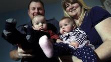 Dominic and Shauna Lussier with their six month old twins, Colton (L) and Brynlea at their home in Winnipeg Manitoba, December 3, 2014. Shauna gave birth six months ago to healthy twins using a donor's eggs. The Winnipeg government employee and her husband travelled to the Czech Republic for the $8,000 procedure after a miscarriage and unsuccessful fertility treatments in Canada. (Lyle Stafford For The Globe and Mail)