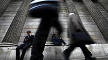 A man and woman use their mobile phones as commuters walk past the columns of the Bank of England in the City of London, July 3, 2012. (ANDREW WINNING/REUTERS)